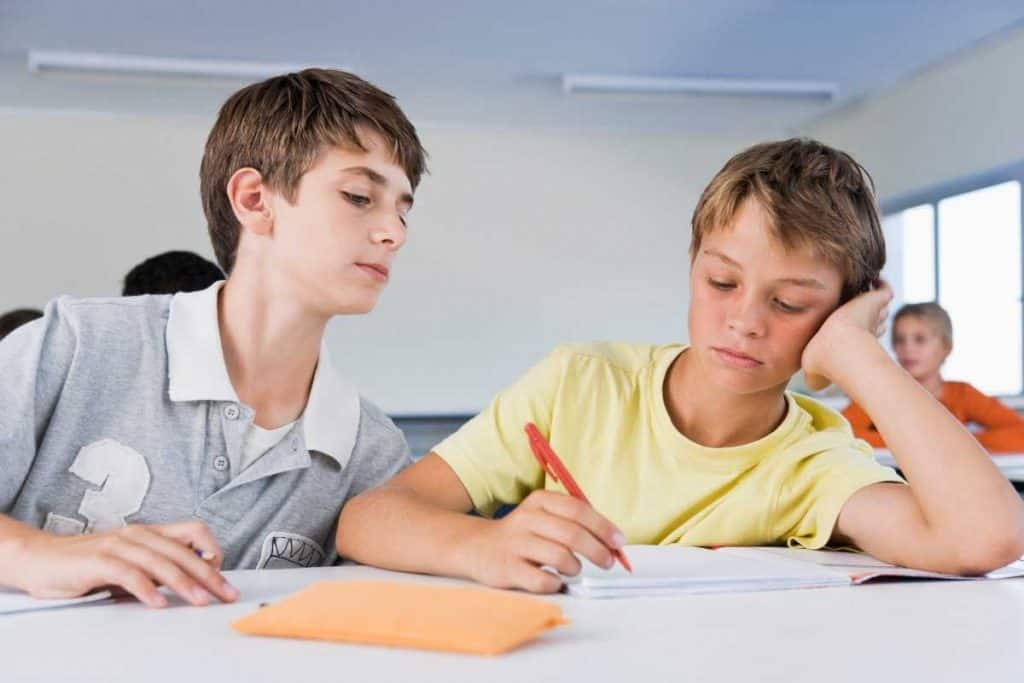 Boy copying test from classmate