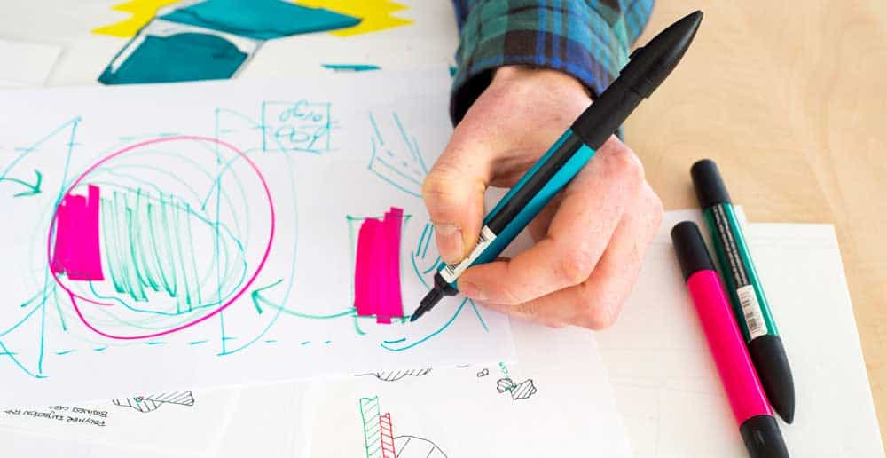 close up of man drawing a product for development