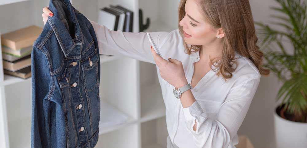 woman poses to take photo of jacket she bought on store