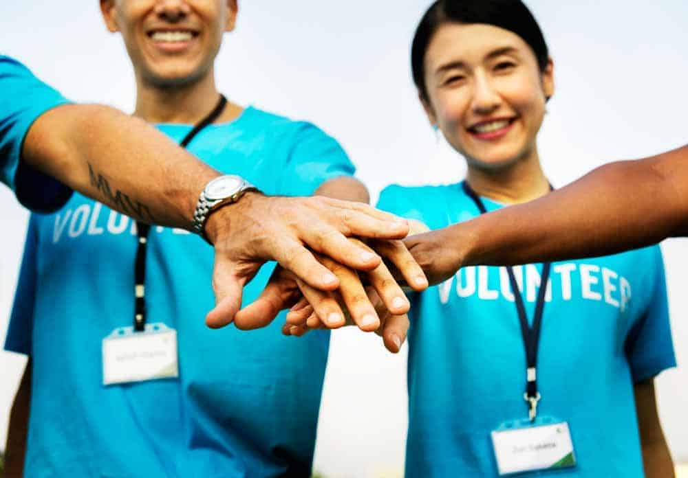 nonprofit team stacking hands together