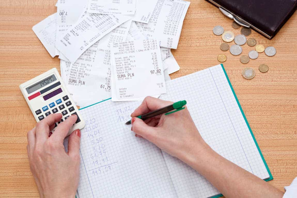 man calculates expenses to cut business costs