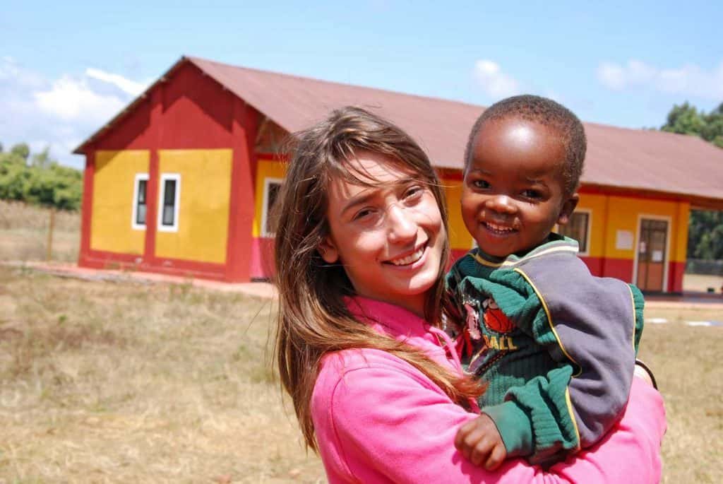 woman for a nonprofit organization holding a child