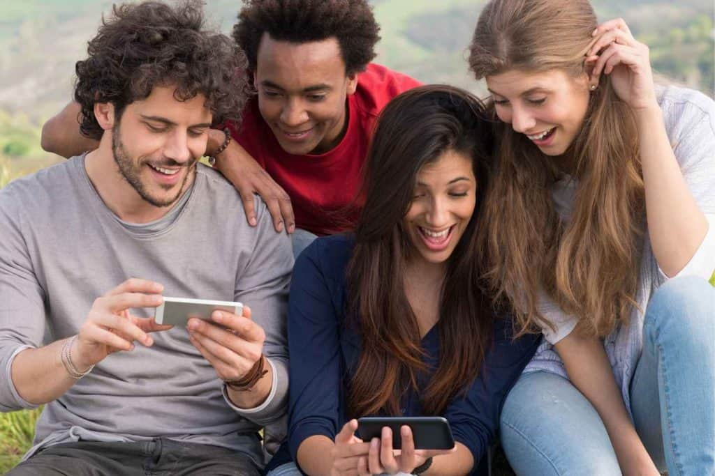 Friends looking at cellphone viral content